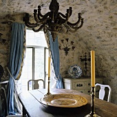Old arched ceiling in rustic dining room and blue curtains as the window
