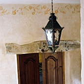 Ceiling lantern in front of an apricot colored wall with border and wooden lentil over a door to a room