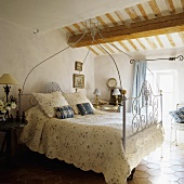 A white, antique four poster bed under and wooden beam in an attic room in a country house