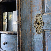 Detail of a piece of old wooden furniture with blue paint and a lock with a decorative frame and a key
