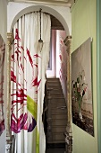A flower pattern on a curtain in an archway to a stairwell
