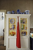 Blue crockery on a painted kitchen cupboard with a red apron hanging from the door