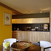 A fitted kitchen with light wooden fronts and wooden handles in front of a dark grey wall with spotlights in the ceiling
