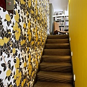 A narrow stairway with a flower-patterned papered wall and a yellow-painted wall with a view onto a chair