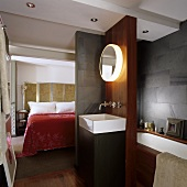 A bedroom with an en-suite bathroom - a wash basin with wall lighting in a partition wall with a view of the bed