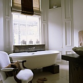 Free standing bathtub on wooden blocks and an antique white chair in front of window in a light gray bathroom