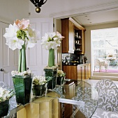 White amaryllis in a glass vase on a glass table with open swing doors and view of a fitted kitchen