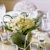 A bunch of white roses and decorative grass in a glass vase surrounded by tea lights