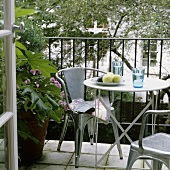 Metal chairs around a bistro table on a balcony with a garden view