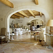 A view through a round archway in a Mediterranean living room with a rustic wooden ceiling, a white sofa and a terracotta floor