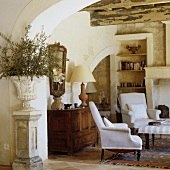A view through a round archway into a corner of a rustic living room with white armchairs in front of a wooden sideboard