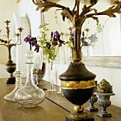 A glass carafe and an antique candlestick on a wooden shelf