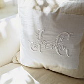 A white cushion embroidered with initials
