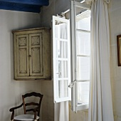 An old fashioned wall cupboard in a corner next to an open window