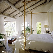A bedroom with a rustic wooden and a white, bamboo four poster bed with a view of a garden