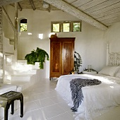 A cool white bedroom in a tropical holiday home with an antique wooden cupboard and a flight of stairs