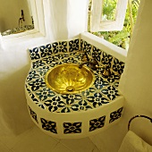 A corner of a bathroom with a tiled wash basin and a brass basin