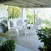 Elegant white, Spanish style terrace furniture on the wooden terrace of a holiday home