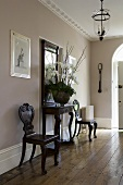 An elegant hallway with dark antique chairs, a wall table and old floor boards