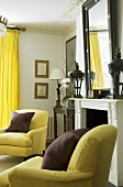 Dark red cushions on yellow armchairs in front of a fireplace with bright yellow curtains at the window