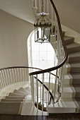 Chandelier in a stair well in a curved staircase with carpet runners
