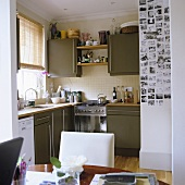 A dining room with a kitchen in the background with grey cupboards