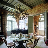 Living room with stone table and antler chandelier in a French country home