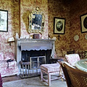 A sooty fireplace in a living room in a country house with patterned paper on the wall