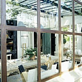 A view through a metal transom window onto an extension with a dining table