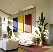 A living room in a Mediterranean house - designer furniture in front of a concrete wall with solid colour abstract artwork