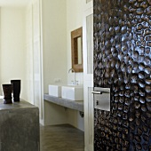 A view through an open door with a structured surface onto a counter and a concrete wash basin