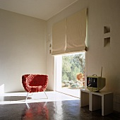 A red scraggy chair standing in a patch of light from a floor-to-ceiling window in a designer living room