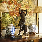 A wooden African figure and table lamps with straw shades on a wall table next to two jars