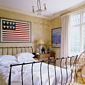 A bed with a metal frame in front of a yellow wall with a stylized American flag