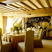 An old English mill house - covered chairs around a laid table in an open-plan living room with a wood beam ceiling