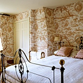 Bedroom with antique iron bed in front of wall covered with patterned wallpaper (country home style decor)