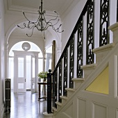 A flight of stairs with black, wrought iron banisters and a chandelier with Medusa arms in front of an archway
