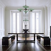 A dining table with a wooden frame and benches with leather cushions in an elegant living room with an art deco-style ceiling lamp