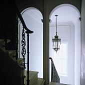 Weisses Treppenhaus mit Rundbögen und Blick auf Deckenlaterne