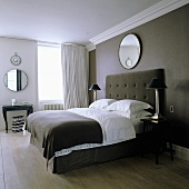 A double bed with a high, upholstered headboard against a dark wall with a mirror hanging above it