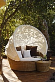 Relaxation on a terrace in a wicker armchair with a white sun shade