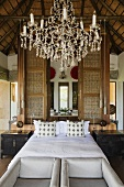 A chandelier and a double bed in front of a room divider with a view into a bedroom in a South African house
