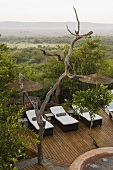 Loungers on a wooden terrace with bamboo umbrella and view of the South African landscape