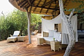 A wicker sofa with a white canopy and rustic wooden supports on the terrace of South African house