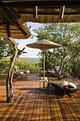 A bamboo sunshade and a lounger on the honey coloured wooden terrace of a South African house