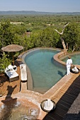 A woman by pool with a wooden terrace and view of the South African landscape