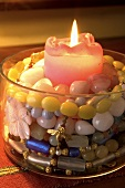 A glass container filled with a colourful beaded necklace and a burning candle