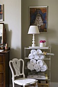 An old chair and a white table lamp and hand towels on metal shelf in front of a grey wall