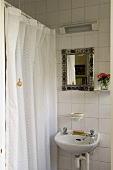 A wash basin and a mirror on a white tiled wall next to a close shower curtain