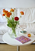 Orange flowers in a glass vase on a white bistro table in front of an upholstered sofa